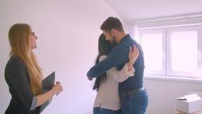 Weibliche Immobilienagentur, welche die Schlüssel von der neuen Wohnung zu den glücklichen jungen Paar- und Erschütterungshänden  stock video footage