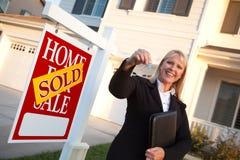 Weibliche Immobilienmakler-überreichende Haus-Tasten Stockfoto