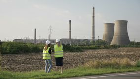 Weibliche Ingenieure des Projektleiters mit Sturzhelm den Plan des Industriebaustandorts analysierend - stock video footage