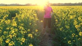 Weibliche junge Frau des Afroamerikanermädchenjugendlichen, die eine Flasche Wasser auf dem Gebiet von gelben Blumen laufen lässt stock video footage
