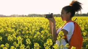 Weibliche junge Frau des Afroamerikanermädchenjugendlichen, die Foto auf dem Gebiet von gelben Blumen macht stock video