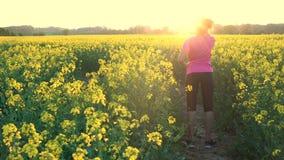 Weibliche junge Frau des Mischrasse-Afroamerikanermädchenjugendlichen, die eine Flasche Wasser auf dem Gebiet von gelben Blumen t stock video footage