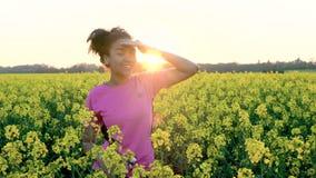 Weibliche junge Frau des Mischrasse-Afroamerikanermädchenjugendlichen, die eine Flasche Wasser auf dem Gebiet von gelben Blumen t stock footage