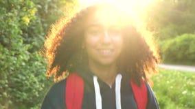 Weibliche junge Frau des schönen glücklichen Mischrasse Afroamerikanermädchenjugendlichen, die mit rotem Rucksack im Land bei Son stock footage