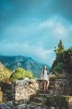 Weibliche junge romantische Frau, die in alte Stange, Montenegro geht Brunettefrau mit dem langen Haar, das auf alten Ruinen aufw Lizenzfreie Stockbilder