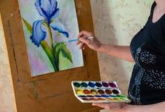 Weibliche Künstlermalerei auf Segeltuch in der Werkstatt an stockbilder