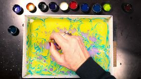 Weibliche Künstlermalerei ebru Technik - Kunst auf Wasser Zeitversehen Zeichnung mit der Bürste gefolgt von den Papierdrucken bun stock video footage