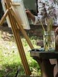 Weibliche Künstlermalerei im Garten Lizenzfreie Stockfotografie