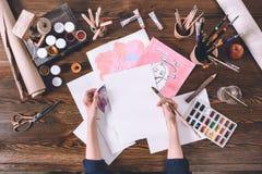 Weibliche Künstlermalereiskizzen am Arbeitsplatz mit Farben und Bürsten Stockfotos