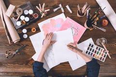 Weibliche Künstlermalereiskizzen am Arbeitsplatz mit Farben und Bürsten Stockfotografie