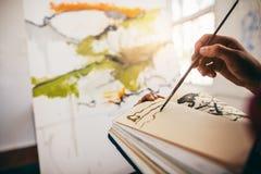 Weibliche Künstlerzeichnungsbilder im Buch Lizenzfreies Stockbild