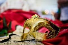 Weibliche Karnevalsmaske, die auf Musikblatt legt Lizenzfreies Stockbild