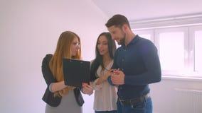 Weibliche kaukasische Immobilienagenturvertretung und Beschreibung der Wohnung zu den jungen kaukasischen Paaren stock footage