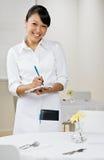 Weibliche Kellnerin nimmt Ordnung Stockbild