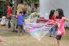Weibliche Kinder, die Ballone einer große Seife spielen lizenzfreie stockfotos