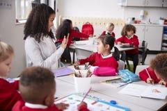 Weibliche Kindergärtnerin, die bei Tisch in einem Klassenzimmer spricht und gestikuliert zu einem jungen chinesischen Schulmädche lizenzfreie stockfotografie