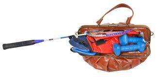 Weibliche kleine Handtasche mit den Sporteinzelteilen lokalisiert Stockfotografie