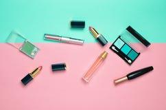Weibliche Kosmetik für Make-upplan auf einem Pastellhintergrund Kosmetische Schatten, Make-upbürste, Lidschattenlippenstift, Parf stockfotografie