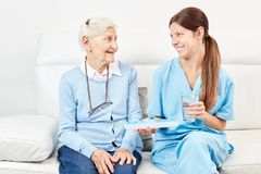 Weibliche Krankenschwester gibt älterer Droge eine Droge stockfoto