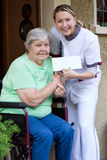 Weibliche Krankenschwester und Patient in einem Rollstuhl Lizenzfreies Stockfoto