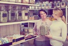 Weibliche Kunden, die verschiedene Kräuter vorwählen Lizenzfreie Stockfotografie