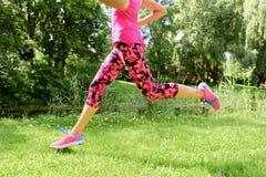 Weibliche Läuferlaufschuhe und -beine in der Stadt parken Stockfotografie