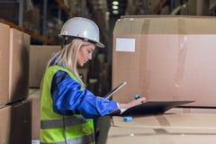 Weibliche Lagerarbeitskraft, die Anmerkungen in den Dokumenten macht Stockfotos
