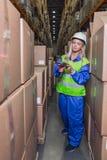 Weibliche Lagerarbeitskraft, die Scanner im Lagerhaus verwendet Stockbilder