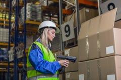 Weibliche Lagerarbeitskraft, die Scanner verwendet Stockbild