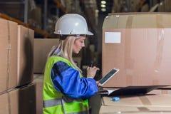 Weibliche Lagerarbeitskraft, die Tabletten-PC verwendet Lizenzfreie Stockfotografie