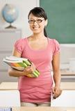 Weibliche Lehrerholdingbücher im Klassenzimmer Lizenzfreie Stockfotografie