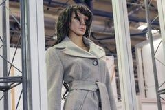 Weibliche Mannequins in einem modischen Mantel im Speicher lizenzfreie stockfotografie