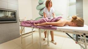 Weibliche Masseuse, die Massage mit heißen Steinen tut lizenzfreies stockbild