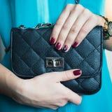 Weibliche Nägel mit rotem Nagellack und einer schönen schwarzen Handtasche lizenzfreie stockfotos