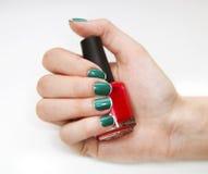 Weibliche Nagelkunst mit nettem Funkeln-, Grünem und weißemNagellack stockbilder
