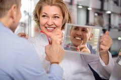 Weibliche Optikerhilfen wählen Sie den Rahmen eines reifen männlichen Kunden stockbilder
