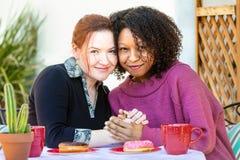 Weibliche Paare, die bei Tisch zusammen sitzen Stockfotografie