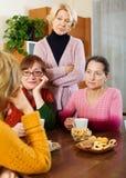 Weibliche Pensionäre, die auf traurige Geschichte ihres Freunds hören Lizenzfreie Stockfotos