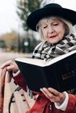 Weibliche Person der Art im Ruhestand, die Bibel betrachtet lizenzfreies stockfoto