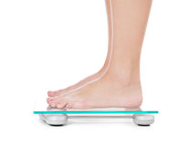 Weibliche Person, die auf Gewichtskala steht Stockfotos