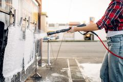 Weibliche Person mit Wasserwerfer säubert Automatten stockfotos