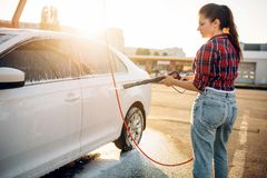 Weibliche Person waschen weg den Schaum vom Auto lizenzfreie stockbilder