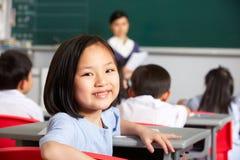 Weibliche Pupille, die am Schreibtisch in der chinesischen Schule arbeitet lizenzfreies stockfoto