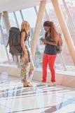 2 weibliche Reisende in der Flughafenhalle Telefon überprüfend Lizenzfreie Stockbilder