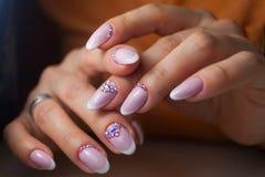 Weibliche rosa französische Maniküre auf schönem Hintergrund stockfotos