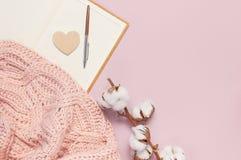 Weibliche rosa gestrickte Strickjacke, Baumwolle, offenes leeres Notizbuch, Stift auf rosa flacher Pastelllage der Draufsicht des stockbild