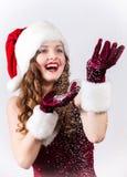 Weibliche Sankt, die ein schneebedecktes Weihnachten genießt Lizenzfreie Stockfotos