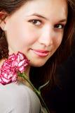 Weibliche Schönheit und rote Gartennelkeblume Lizenzfreies Stockfoto