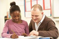 Weibliche Schüler, die im Klassenzimmer mit Lehrer studiert Stockbild