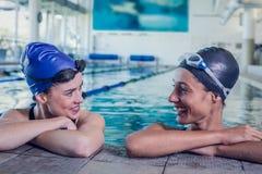 Weibliche Schwimmer, die an einander im Swimmingpool lächeln Stockfotografie